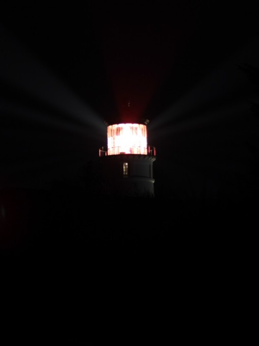 Red and white beams visible from the lighthouse